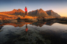 Unrecognizable Female Tourist Admiring Highland While Standing On Mountain Near Pure Pond Under Sky At Sunset