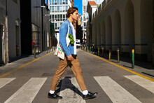Full Body Side View Of Handsome Young Male In Stylish Outfit With Reusable Textile Bag With Groceries Crossing Road In Modern City District
