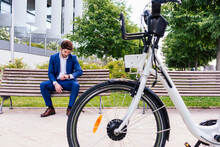 Handsome Businessman In Elegant Clothes Sitting On Wooden Bench While Checking Time Near Electric Bike In Town