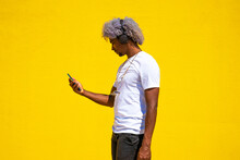 Black Man With Afro Hair Listening To Music With Earphones On A Yellow Background. Listening To Music.