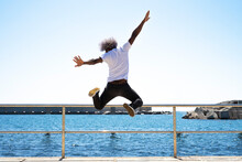 Black Man With Afro Hair Jumping In Front Of The Sea And The Beach. Concept Of Jumping In Front Of The Sea. Blue Tones.