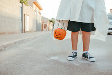 Cropped Unrecognizable Kid In White Ghost Costume And With Plastic Jack O Lantern Standing In City On Halloween In Autumn