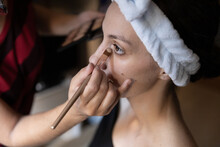 Cropped Unrecognizable Professional Stylist Applying Concealer On Female Customer Lower Lid By Using Brush In Studio
