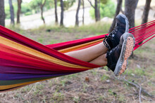 Crop F Delighted Female Lying And Swinging In Hammock In Green Garden On Sunny Day While Having Sun And Looking Away