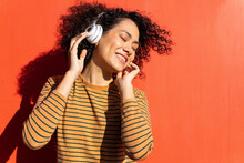 Happy Trendy Ethnic Female With Closed Eyes And Afro Hairstyle Enjoying Song In Headset On Red Background