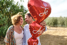 Tender Mature Couple Standing Together In Garden With Red Air Balloons In Shape Of Heart And Looking At Each Other During Stroll
