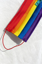 From Above Of Detail Of Vivid Protective Mask With Picture Of Rainbow Flag Placed On Bed At Home