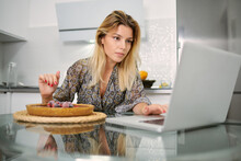 Focused Young Female Garnishing Homemade Vegan Tart With Frozen Berries While Sitting At Table With Laptop In Home Kitchen