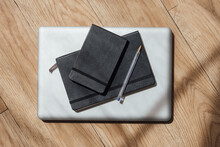 Top View Composition Of Notepads In Black Cover Arranged With Pen On Contemporary Netbook On Parquet