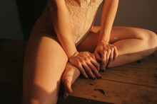 Cropped Unrecognizable Sensual Slender Female Wearing Lace Bodysuit Sitting Barefoot On Wooden Table In Room And Looking Away