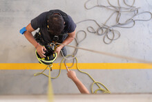 Top View Of Unrecognizable Fireman With Helmet And Rope Near Crop Colleague Pointing With Finger During Practice At Work