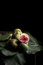 From Above Of Fresh Sweet Figs Arranged On Green Leaves On Black Table