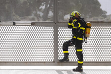 Side View Of Unshaven Firefighter In Colorful Uniform Putting On Hardhat While Standing With Fire Extinguisher Near Grid Fence And Looking Away