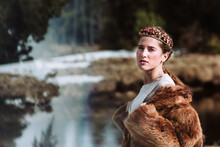 Side View Of Beautiful Young Female With Braided Hairstyle And Floral Wreath Wearing Warm Fur Coat Standing Against Blurred Environment Of Early Spring Forest And Looking At Camera