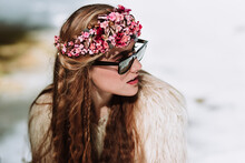 Attractive Young Long Haired Female In Fur Jacket And Sunglasses With Floral Wreath On Head Sitting On Snowy Meadow In Coniferous Forest In Sunny Early Spring Day