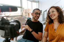 Side View Of Focused Young Couple Blogger With Curly Hair In Casual Outfit And Eyeglasses And Professional Photo Camera Placed On Tripod While Shooting Video At Home