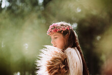 Side View Of Charming Romantic Young Long Haired Female With Pink Floral Wreath Standing In Forest Looking Away