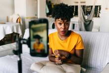 Cheerful Young African American Female Blogger Recording Video On Smartphone While Preparing Content For Social Networks At Home