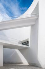 Low Angle White Minimalist Building Wall In Futuristic Style With Narrow Inclined Ramp Located Under Blue Sky