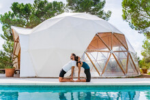 Side View Of Unrecognizable Fit Man And Woman Standing In Ustrasana Pose While Practicing Yoga And Reflecting In Swimming Pool Near Tent