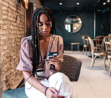 Young African American Female With Afro Pigtails Wearing Trendy Clothes Sitting On Chair And Using Mobile Phone While Resting In Modern Loft Cafeteria