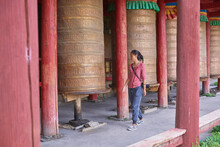 Full Body Of Asian Female Passing By Tibetan Rolls With Ancient Prayer Near Sacred Oriental Temple