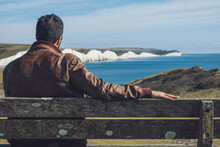 Back View Of Unrecognizable Young Male Tourist In Stylish Outfit Sitting On Wooden Bench And Admiring Seven Sisters Cliffs On Sunny Day