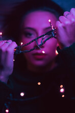 Young Woman Holding Garland With Glowing Bulbs In Dark Studio With Violet Neon Illumination