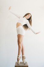 Graceful Female Ballet Dancer In Pointe Shoes Standing On Stool On Tiptoes With Closed Eyes And Outstretched Arms While Balancing And Performing Dance In Studio
