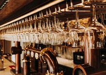 Interior Of Bar With Shiny Glasses Hanging On Metal Rack Over Draught Beer Taps In Restaurant In Madrid