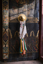 Part Of Old Ancient Tibetan Building With Wooden Gate Painted In Various Ornaments With Golden Handle With Ritual Ribbons