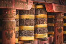 Exterior Of Tibetan Church Decorated With Big Cylindrical Rolls With Stripes And Hieroglyphs Between Red Shabby Columns
