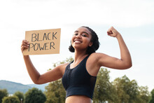 Cheerful Young Sporty Ethnic Lady In Activewear Demonstrating Biceps And Placard With Black Power Text Looking At Camera After Outdoor Training Near Pond In Park
