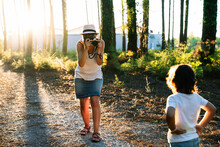 Unrecognizable Young Female Photographer In Casual Clothes And Hat Shooting Adorable Little Son Standing On Alley In Picturesque Park