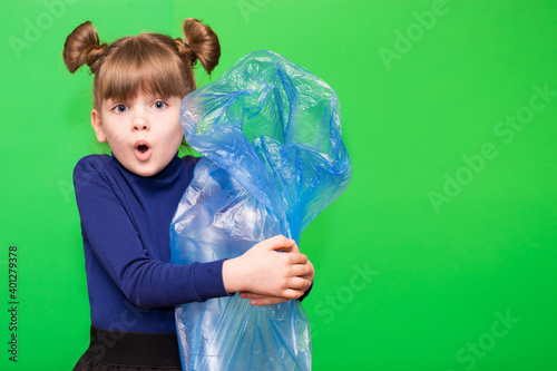 Canvas Print Girl hold trash bag and plastic bottle and shows interest in environmental issues isolated on green background