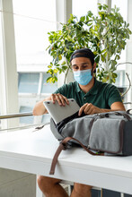Traveling Male In Medical Mask Sitting At Table In Departure Lounge Of Airport And Putting Laptop In Backpack While Waiting For Flight During Coronavirus Epidemic