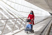 Traveling Female Walking In Airport With Baggage Trolley And Waiting For Flight
