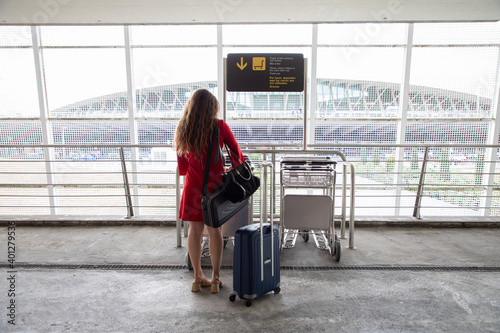 Back view of traveling female in airport collecting a baggage trolley and waiting for flight