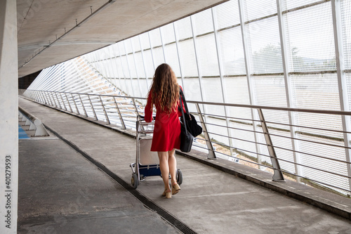 Back view of traveling female walking in airport with baggage trolley and waiting for flight