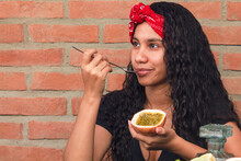Girl With A Red Scarf On Her Head Enjoys The Tropical Flavor Of A Passion Fruit