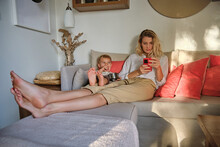 Glad Young Woman With Cellphone Lying On Cozy Sofa With Adorable Little Son Eating Sweets From Metal Jar