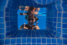 From Below Underwater Shot Of Delighted Boy Giving Thumbs Up Through Transparent Swimming Pool Water