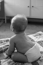 6 Month Old Baby Learning To Sit Up Unassisted; Wearing Diaper Seated On A Quilt