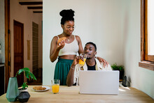 Concentrated Black Male Freelancer Working At Laptop While Thoughtful African American Wife In Crop Top Eating Bun And Looking Away