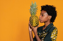 Side View Of Serious Young Black Female Looking Away Holding Pineapple In Stylish Apparel On Orange Background