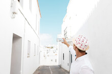 Side View Of Unrecognizable Stylish Tourist In Ornamental Hat Taking Photo Of Old House On Cellphone During Vacation In Rhodes