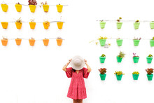 Anonymous Female Tourist Covering Face With Straw Hat Near White Wall With Different Potted Plants