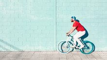 Side View Of Young Active Bearded Male Cyclist In Stylish Outfit Listening To Music In Headphones While Riding Bike On Street Near Blue Stone Building On Sunny Day