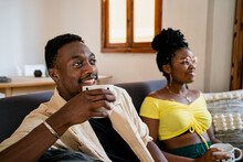 Cheerful African American Friends In Casual Clothing Drinking Tea And Looking Ahead With Bright Smile While Lounging On Sofa In Bright Cozy Room Decorated In Pastel Colors