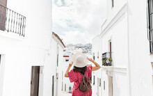 Back View Of Unrecognizable Female Tourist With Raised Arms On Narrow Street Between Old Houses In Greece
